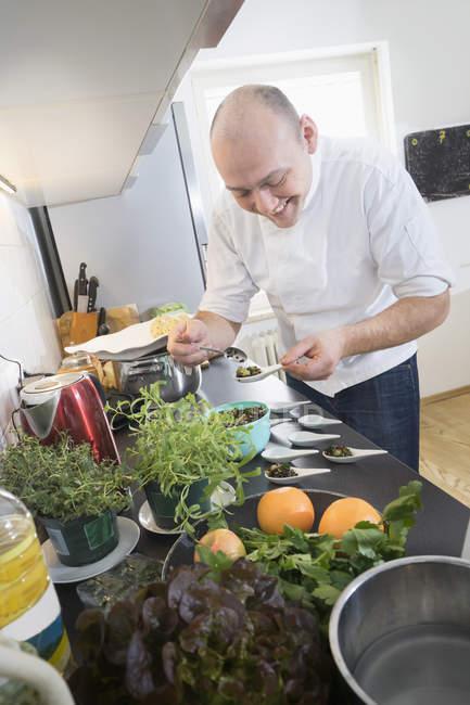 Meados adulto chef para preparar a salada de lentilha na cozinha moderna — Fotografia de Stock