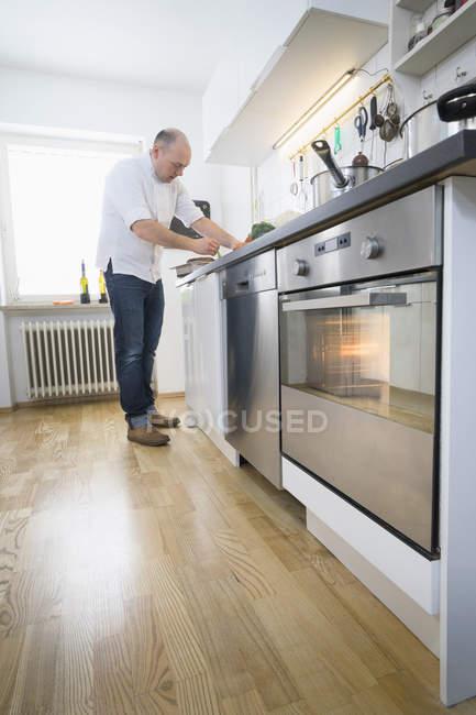 Cozinhar cozinhar no balcão na cozinha moderna — Fotografia de Stock