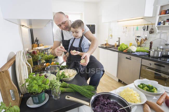 Pai e filho se preparando bolinhos na cozinha moderna — Fotografia de Stock