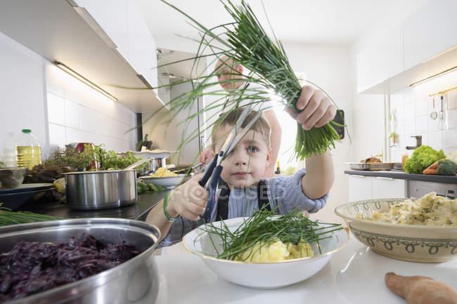 Cebolinho orgânico fresco de elementar idade menino corte com o pai na cozinha — Fotografia de Stock