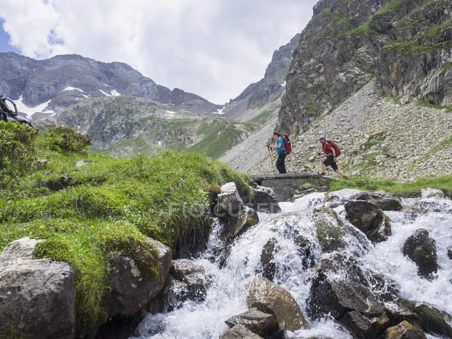 Чоловік і жінка перетину потік гори у високих Піренеях, Котеретс, Франція — стокове фото