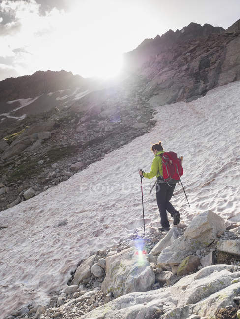 Woman crossing snow field while ascending to mount Vignemale, Cauterets, France — Stock Photo