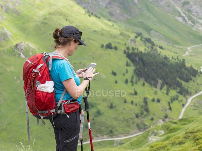 Senderista madura con teléfono móvil en High Pyrenees, Gavarnie, Francia - foto de stock
