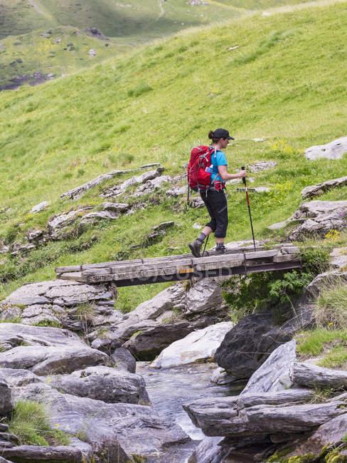 Mujer caminante cruzando el puente de madera en Gavarnie, Francia - foto de stock