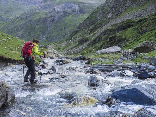 Жінка перетину Дика річка в високий Піренеях поблизу Cirque de Troumouse, Франції — стокове фото