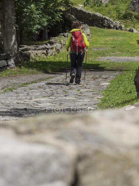 Feminino caminhante caminhando na estrada velha, na aldeia de Heas em Altos Pirineus, França — Fotografia de Stock