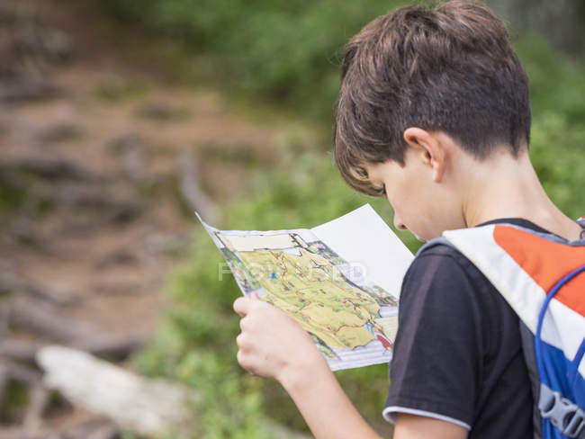 Girl with backpack looking at map in forest — Stock Photo