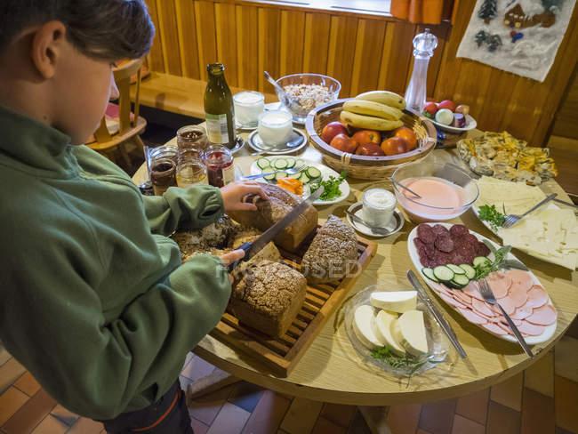 Menina cortando pão enquanto café da manhã na cabana da montanha — Fotografia de Stock