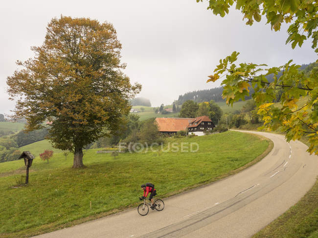 Man riding bicycle in village of Southern Black Forest, Baden-Wurttemberg, Germany — Stock Photo