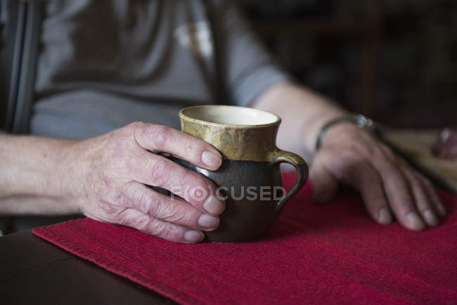 Hands of senior man holding pottery mug — Stock Photo