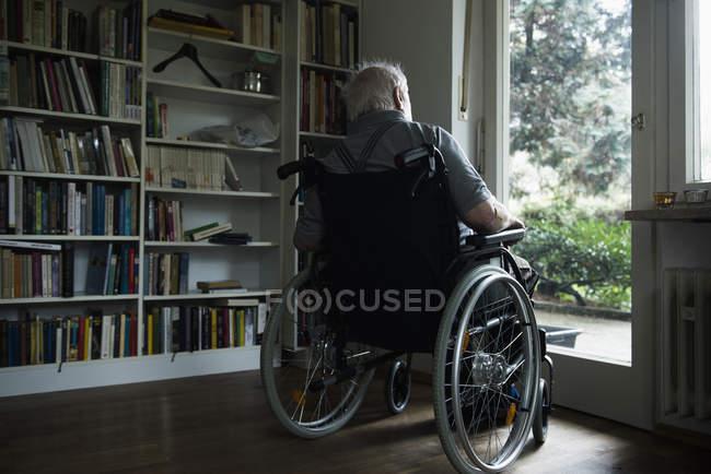 Senior man in wheelchair looking through window at home — Stock Photo