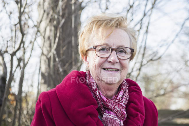 Portrait de femme senior souriant et regardant à huis clos dans parc — Photo de stock