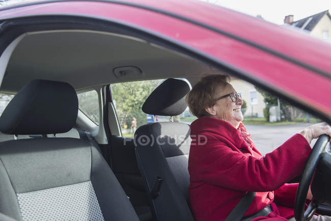Happy senior woman driving car, side view — Stock Photo