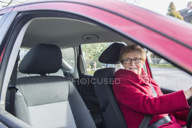 Happy senior woman sitting in car and looking through window — Stock Photo