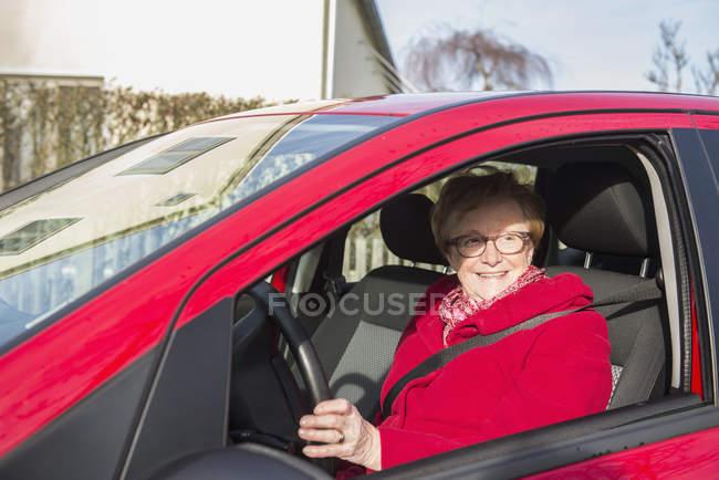 Happy senior woman in red coat driving car — Stock Photo