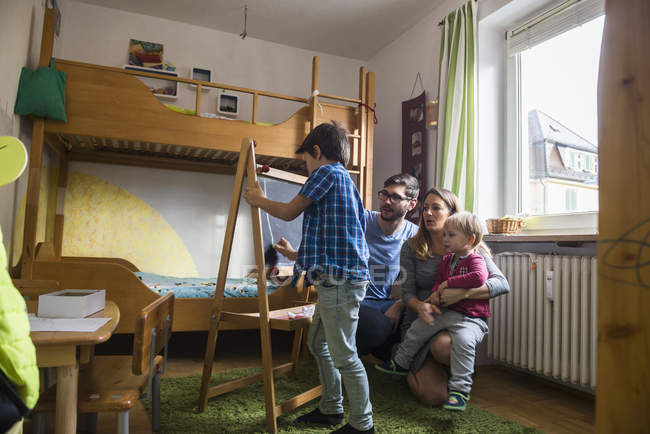 Boy writing on blackboard while parents and toddler brother watching — Stock Photo