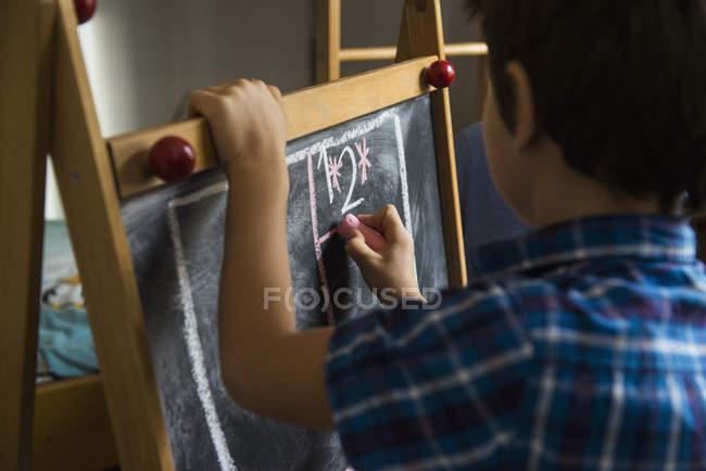 Close-up of boy writing on blackboard — Stock Photo