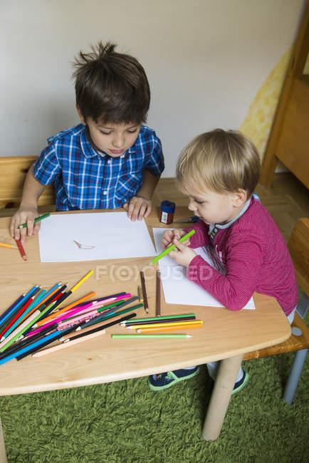 Брати, насолоджуючись креслення з кольорові олівці — стокове фото