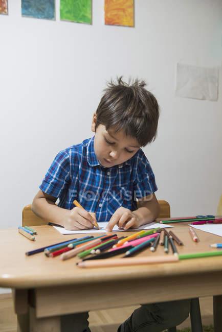 Ragazzo da colorare con le matite colorate al tavolo — Foto stock
