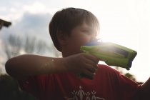 Little boy playing with toy gun — Stock Photo