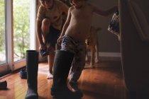 Felices hermanos jugando con botas de goma - foto de stock