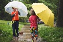 Les petits garçons à pied avec des parapluies — Photo de stock