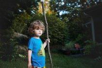 Ragazzo sveglio con il grande albero ramo — Foto stock