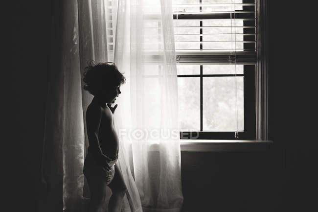 Adorabile bambino in piedi vicino alla finestra — Foto stock