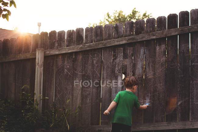 Little boy drawing on wooden fence — Stock Photo