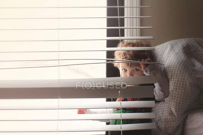 Beau petit garçon debout près de la fenêtre — Photo de stock