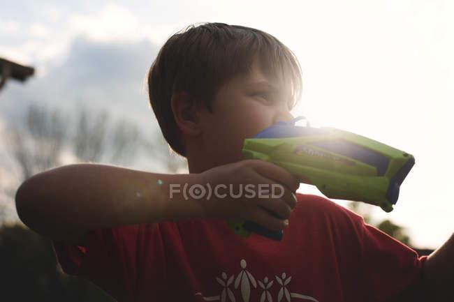 Мальчик играет с игрушечным пистолетом — стоковое фото