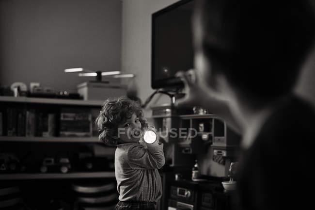 Adorable little boy holding flashlight — Stock Photo