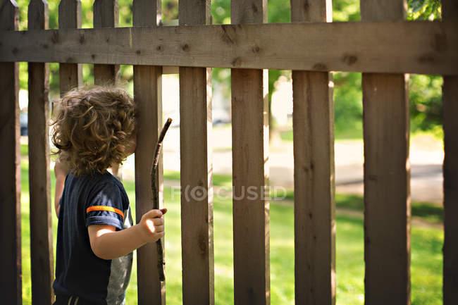 Маленький мальчик смотрит через деревянный забор — стоковое фото