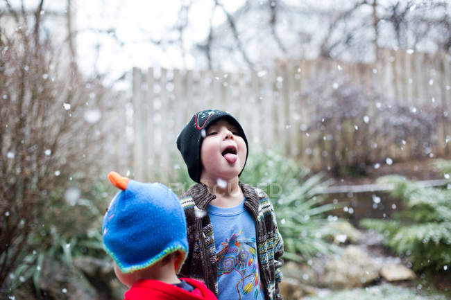 Little boy catching snowflakes with tongue — Stock Photo