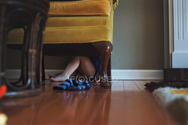 Menino escondido debaixo da poltrona — Fotografia de Stock