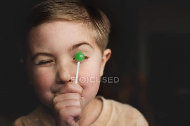 Smiling little boy holding lollipop — Stock Photo