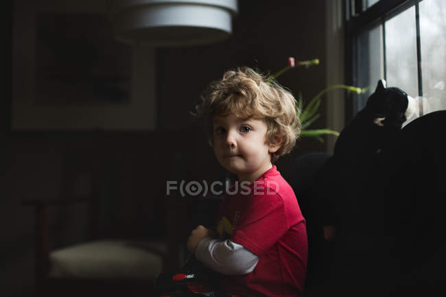 Adorable little boy sitting on sofa — Stock Photo