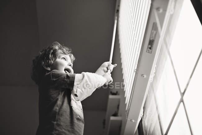 Щасливий маленький хлопчик грає з жалюзі — стокове фото