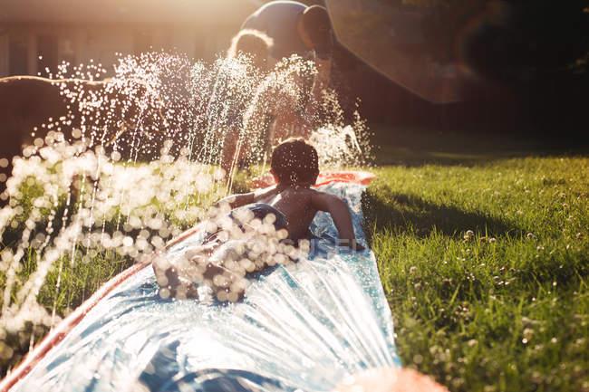 Маленькие братья играют с системой полива — стоковое фото