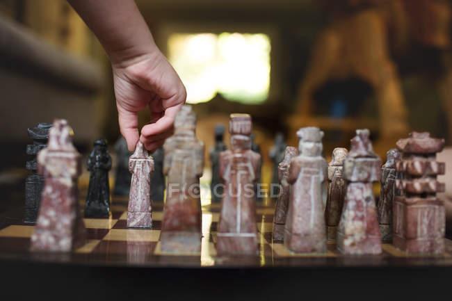 Mão jogando xadrez de mármore — Fotografia de Stock
