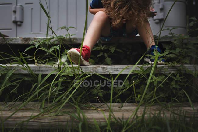 Mignon petit garçon sur les escaliers en bois — Photo de stock