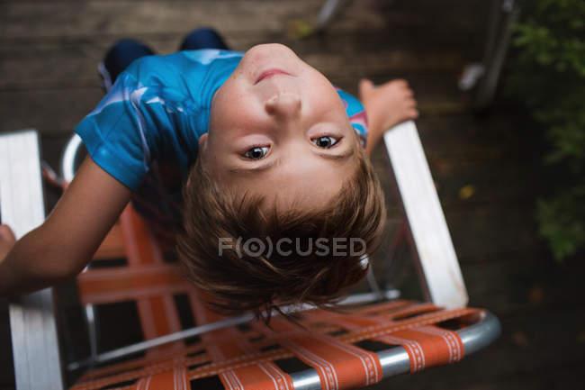 Милый маленький мальчик сидит на стуле — стоковое фото