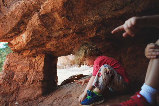 Little boys playing in rocky cave — Stock Photo