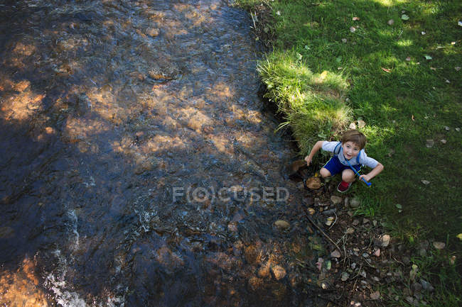 Adorable little boy near mountain river — Stock Photo