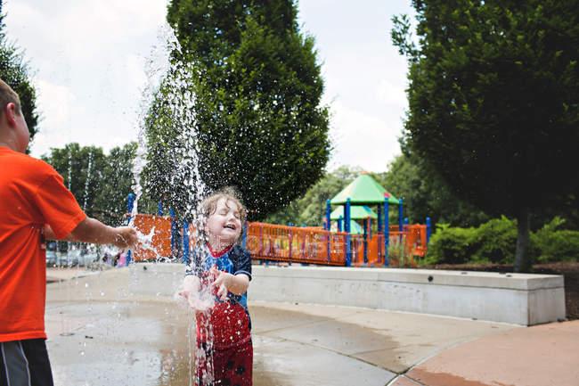 Ragazzi che giocano in fontana — Foto stock