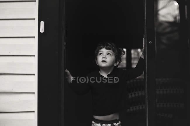 Little boy standing in the doorway — Stock Photo