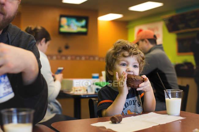 Мальчик ест Шоколад Маффин — стоковое фото