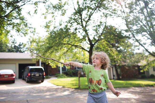 Netter Junge mit Stock auf Straße — Stockfoto