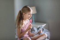 Hermosa chica con tableta digital en el hogar, enfoque en primer plano - foto de stock