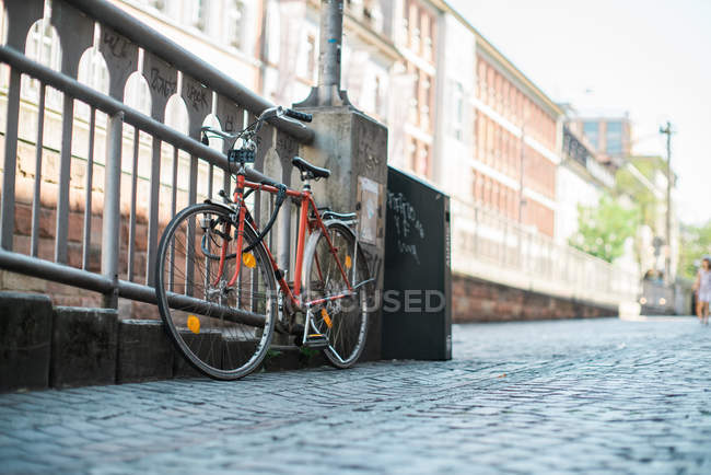 Bicycle parked near fence — Stock Photo